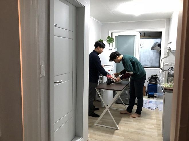 Park cùng một thành viên trong nhóm dọn dẹp sau bữa tối trong căn hộ cả nhóm cùng sống, cũng là văn phòng làm việc của startup. Ảnh: TechinAsia