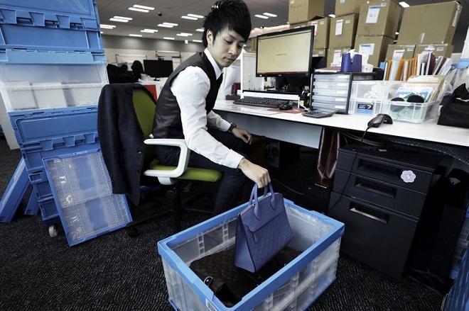 Nhân viên tại Sou đang thẩm định sản phẩm hàng hiệu mới chuyển về. Ảnh: Bloomberg.