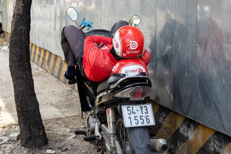 Một tài xế GoViet nghỉ ngơi bên đường. Ảnh: AFP.