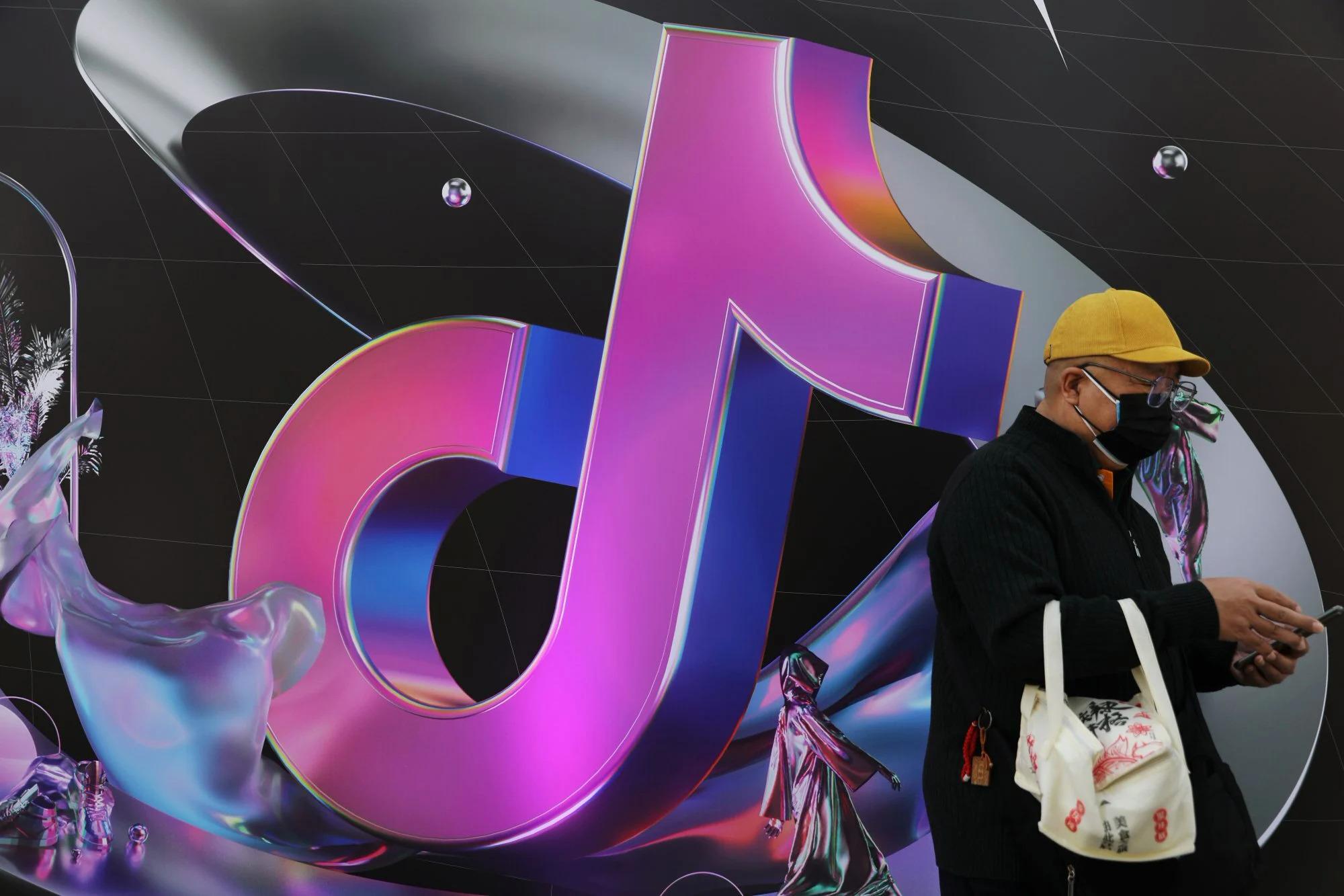 Một người đàn ông đứng gần tấm biển khổng lồ của ứng dụng TikTok của ByteDance, được biết đến với tên gọi địa phương là Douyin, ở Bắc Kinh, Trung Quốc, vào ngày 31 tháng 3 năm 2021. Ảnh: Reuters