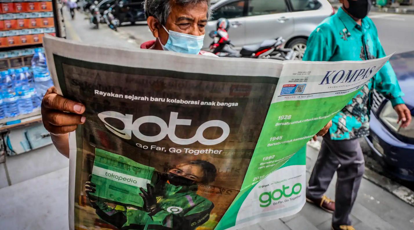 Người dân Indonesia đọc thông tin Gojek và Tokopedia sáp nhập trên một tờ báo địa phương. (Ảnhh: Nikkei).