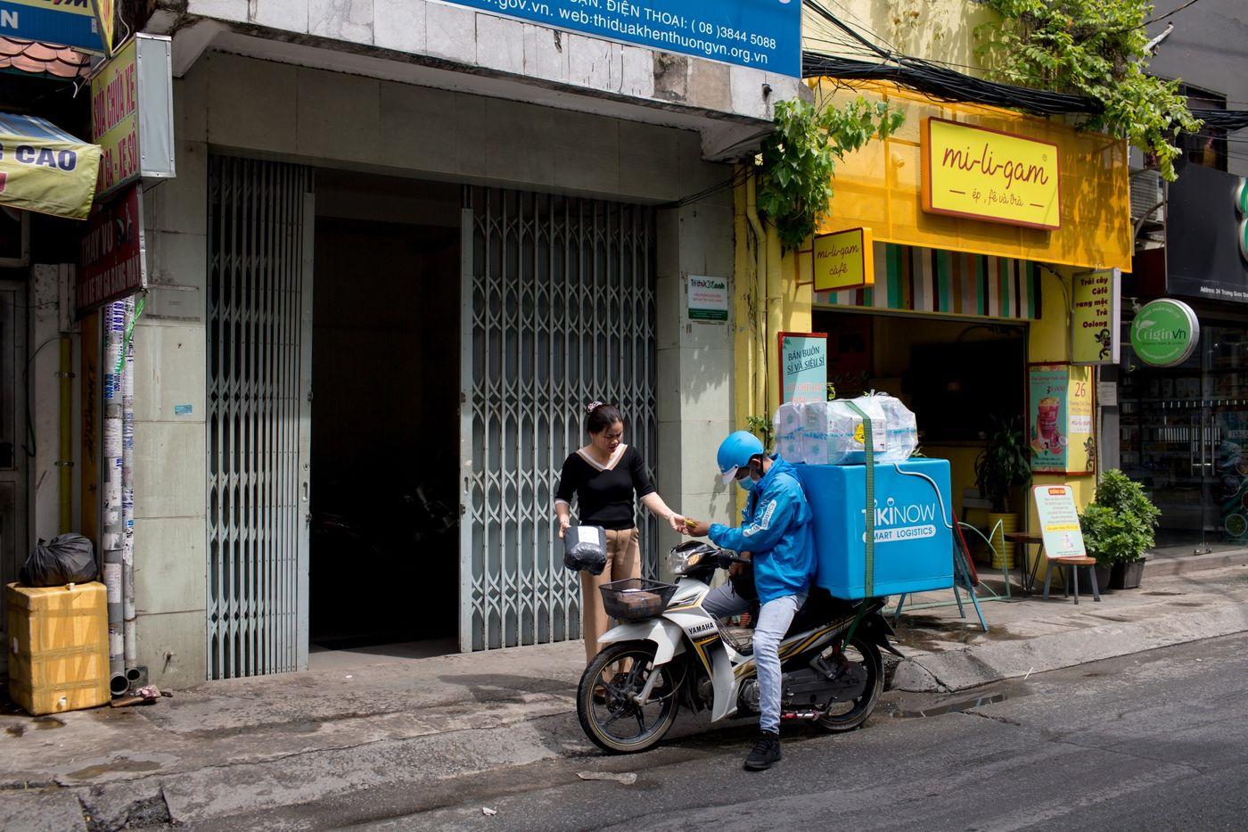 Một nhân viên chuyển phát nhanh của Tiki giao hàng cho một khách hàng ở thành phố Hồ Chí Minh vào ngày 24/5.Nhiếp ảnh gia: Yến Dương / Bloomberg