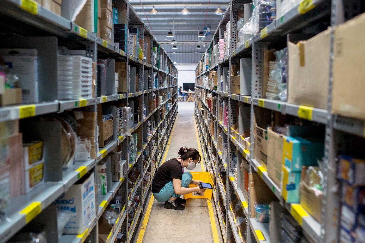 Nhân viên quét dọn và kiểm tra các mặt hàng trên kệ. Ảnh: Yến Dương/Bloomberg.